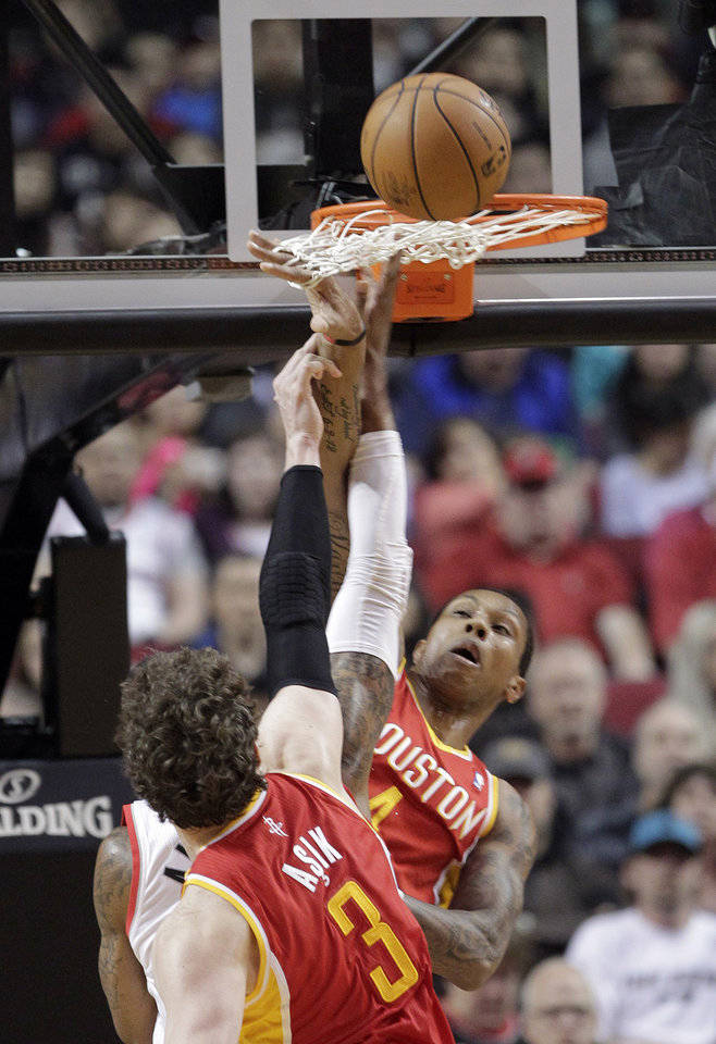 Houston Rockets guard Greg Smith, right, gets his hand caught in the net as he and teammate Omer Asik, left, from Turkey, double-team Portland Trail Blazers forward LaMarcus Aldridge under the basket during the first quarter of an NBA basketball game in Portland, Ore., Friday, April 5, 2013. (AP Photo/Don Ryan)