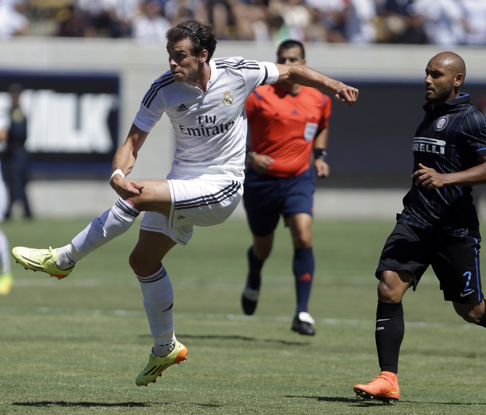 Photo - Real Madrid's Gareth Bale, left, scores ahead of Inter Milan's Jonathan, right, during the first half of a soccer match in the first round of the Guinness International Champions Cup, Saturday, July 26, 2014, in Berkeley, Calif. (AP Photo/Ben Margot)