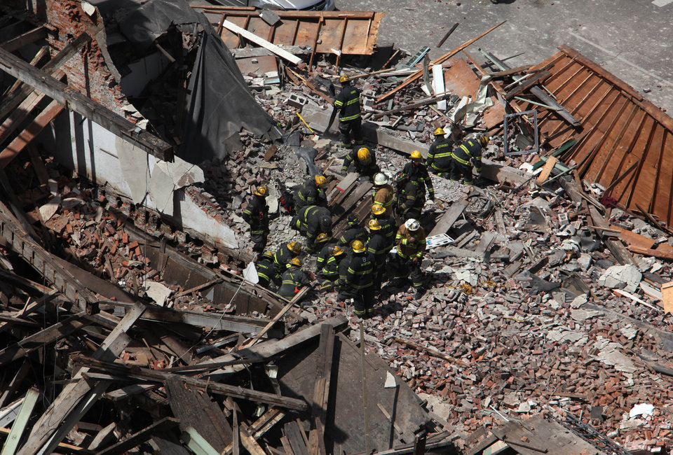 Photo - Rescue personnel work at the scene of a building collapse in  downtown Philadelphia Wednesday June 5, 2013.  A four-story building being demolished collapsed Wednesday on the edge of downtown, injuring 12 people and trapping two others, the fire commissioner said. Rescue crews were trying to extricate the two people who were trapped, city Fire Commissioner Lloyd Ayers said. The dozen people who were injured were taken to hospitals with minor injuries, he said. (AP Photo/Jacqueline Larma)