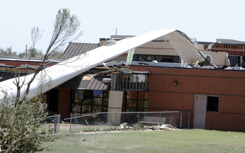 Photo - The blade of a wind turbine rests on top of the day care center at the Canadian Valley Technical Center in El Reno, Okla., on June 1, 2013. The blade was fixed to the ground for training purposes but was blown onto the building during the May 31, 2013, tornado that damaged the CareerTech. Photo by Aliki Dyer, The Oklahoman  Aliki Dyer - The Oklahoman