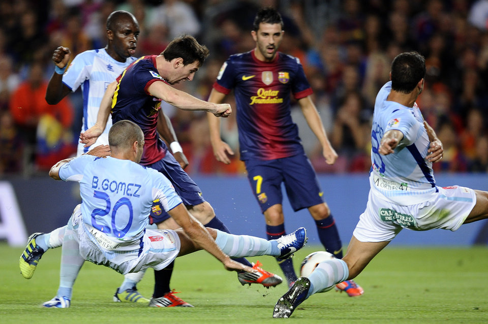 Photo -   FC Barcelona's Lionel Messi from Argentina, third left, duels for the ball against against Granada's Borja Gomez, left, during a Spanish La Liga soccer match at the Camp Nou stadium in Barcelona, Spain, Saturday, Sept. 22, 2012. (AP Photo/Manu Fernandez)