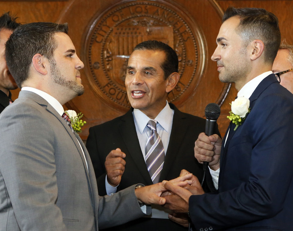 Photo - Jeff Zarrillo, left, and Paul Katami are married by Los Angeles Mayor Antonio Villaraigosa, center, Friday June 28, 2013 at City Hall in Los Angeles. A three-judge panel of the 9th U.S. Circuit Court of Appeals issued a brief order Friday afternoon dissolving,