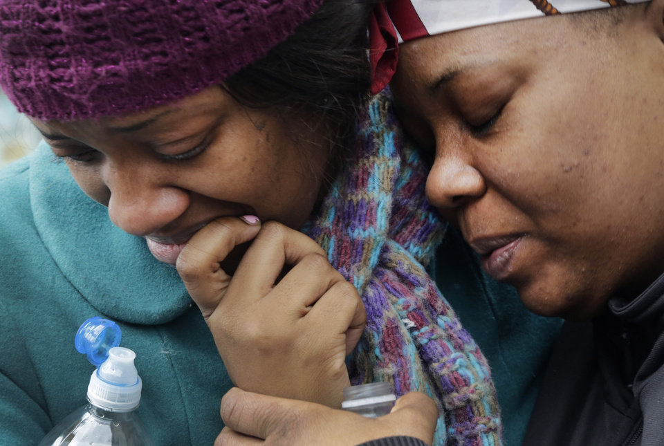 Photo - Alecia Thomas, left, is comforted by her friend, Shivon Dollar, after she lost her home following an explosion that leveled two apartment buildings in the East Harlem neighborhood of New York, Wednesday, March 12, 2014. Con Edison spokesman Bob McGee says a resident from a building adjacent to the two that collapsed reported that he smelled gas inside his apartment, but thought the odor could be coming from outside. (AP Photo/Mark Lennihan)
