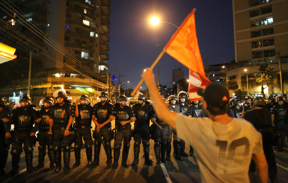 Photo - An anti-World Cup demonstrator waves a flag in front of police lined up near Maracana stadium where a World Cup soccer match is taking place in Rio de Janeiro, Brazil, Sunday, June 15, 2014. Demonstrators are protesting the money Brazil spent on the international soccer tournament and demanding better public services. (AP Photo/Leo Correa)