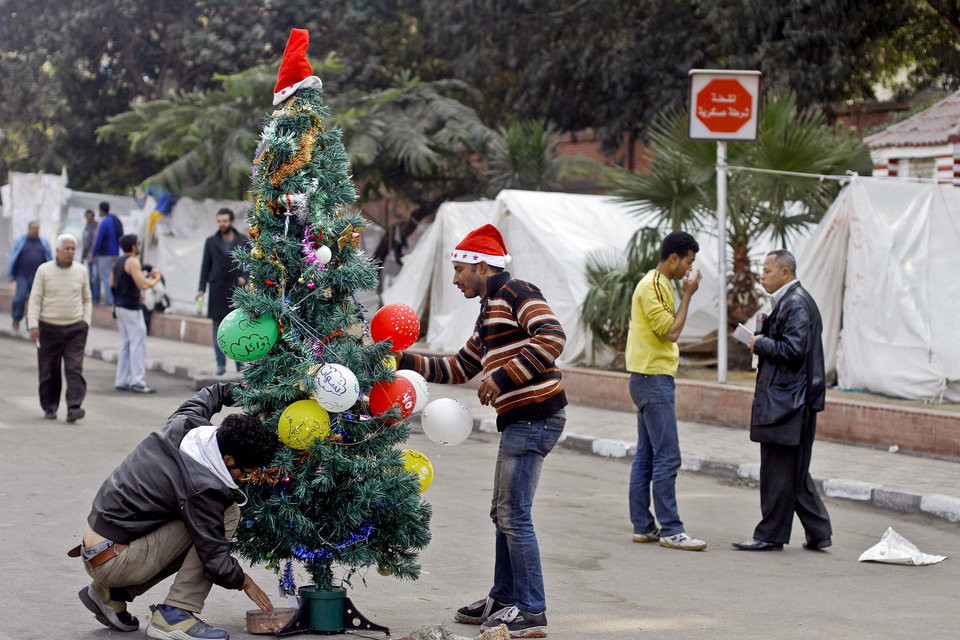 Photo - Egyptian protesters decorate a Christmas tree near the presidential palace in Cairo, Egypt, Monday, Dec. 31, 2012. Protesters will celebrate New Year's eve in front of the presidential palace. (AP Photo/Amr Nabil)