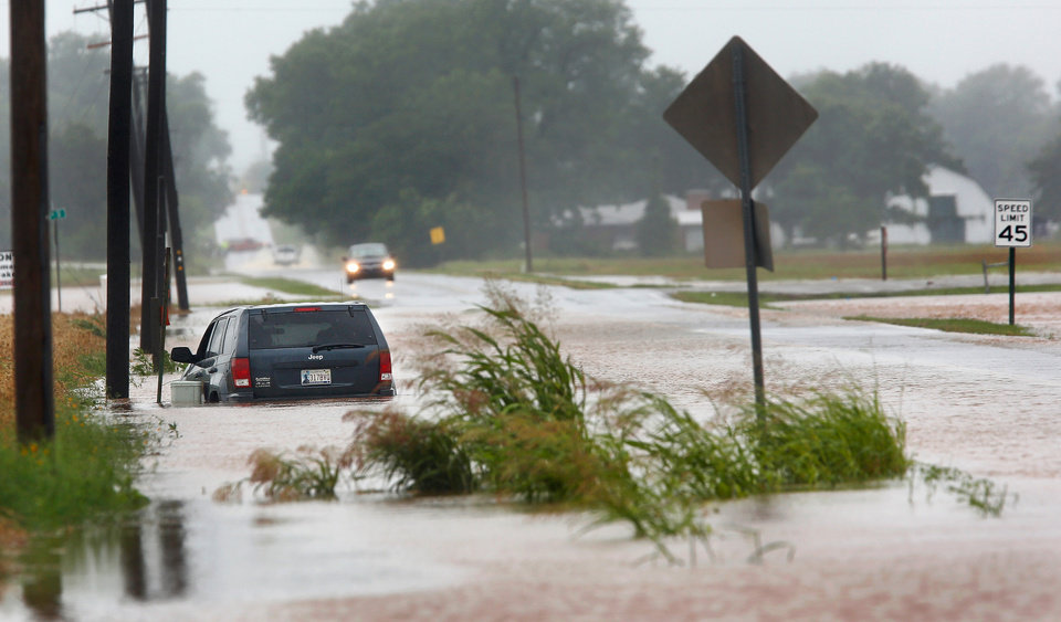 Photo - A vehicle is pointed the wrong direction after high water pushed it into a ditch on the south side of Hardesty Road west of US 177 in Shawnee. Rain from Hurricane Bill produced localized flooding in areas of Pottawatomie County on Thursday, June 18,  2015.   Hardesty Road and US 177. Photo by Jim Beckel, The Oklahoman.