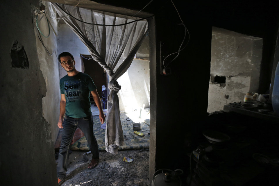 Photo - A Palestinian inspects the damage by an Israeli strike at the Inteiz family house in the Shajaiyeh neighborhood of Gaza City, northern Gaza Strip, Friday, July 18, 2014. Three members of the family, Abd Ali Inteiz, 23, Mohammed Salem Inteiz, 2, and Mohammed Ibrahim Inteiz, 12, were killed overnight when a tank shell hit the family house, according to the family. (AP Photo/Lefteris Pitarakis)