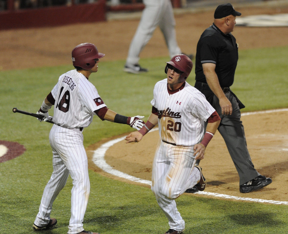Photo - South Carolina's LB Dantzier (20) scores the third run as he is greeted by Dante Rosenberg (18) in the third inning of an NCAA college super regional baseball tournament game against Oklahoma in Columbia, S.C., Saturday, June 9, 2012. (AP Photo/Mary Ann Chastain) ORG XMIT: SCMC104