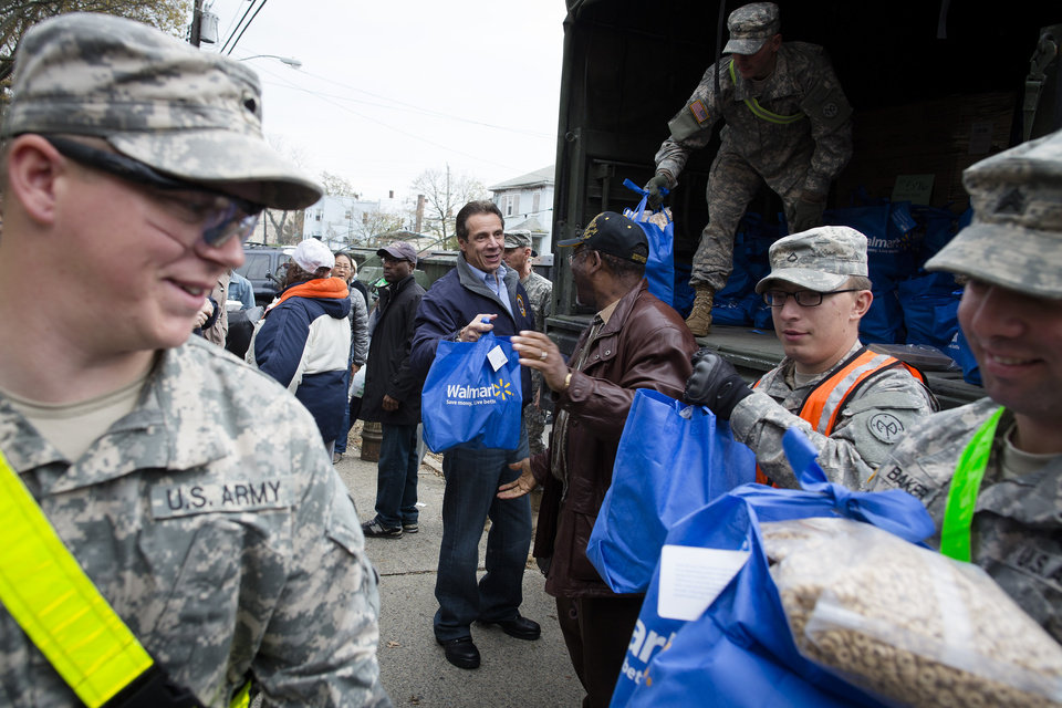Photo -   New York Governor Andrew Cuomo assists the National Guard unload a truck of supplies in the Far Rockaways section of the Queens borough of New York, Saturday, Nov. 10, 2012. Despite power returning to many neighborhoods in the metropolitan area, residents of the Far Rockaways continue to live without power and heat due to damage caused by Superstorm Sandy.(AP Photo/John Minchillo)