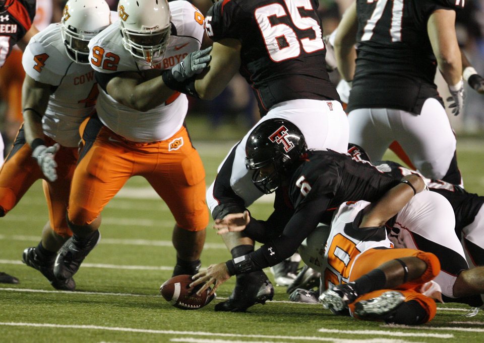 Photo - Graham Harrell loses the ball during the first half of the college football game between the Oklahoma State University Cowboys (OSU) and the Texas Tech Red Raiders at Jones AT&T Stadium on Saturday, Nov. 8, 2008, in Lubbock, Tex.  Patrick Lavine made the recovery.  Andre Sexton is under Harrell.By Steve Sisney/The Oklahoman
