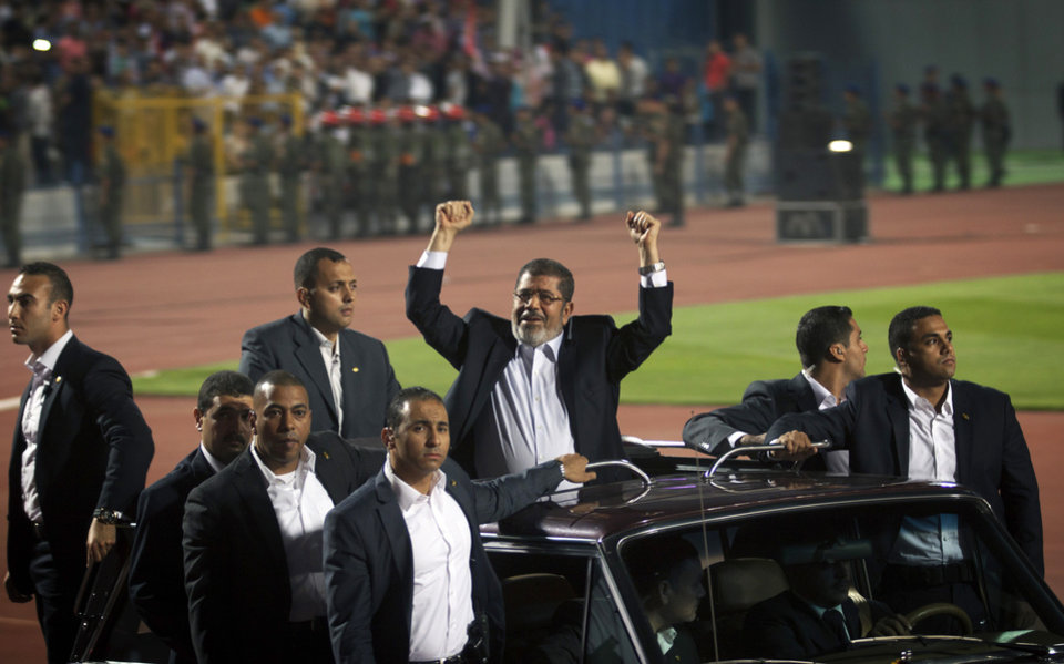 Egyptian President Mohammed Morsi waves to the crowd gathered in a stadium upon his arrival for a speech on the 6th of October national holiday marking the 1973 war with Israel, Cairo, Egypt, Saturday, Oct. 6, 2012.(AP Photo/Khalil Hamra)