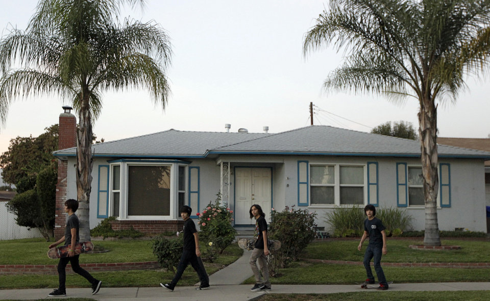 Photo -   Unidentified teens walk past the home of the family of Arifeen David Gojali in Pomona, Calif., on Tuesday, Nov. 20, 2012. Three California men excited at the prospect of training in Afghanistan to become terrorists prepared, authorities say, by simulating combat with paint ball rifles, wiping their Facebook profiles of any Islamic references and concocting cover stories. Family members told The Associated Press they were shocked by Gojali's arrest, but added that the unemployed Gojali had drifted away from the family in the recent months. (AP Photo/Damian Dovarganes)