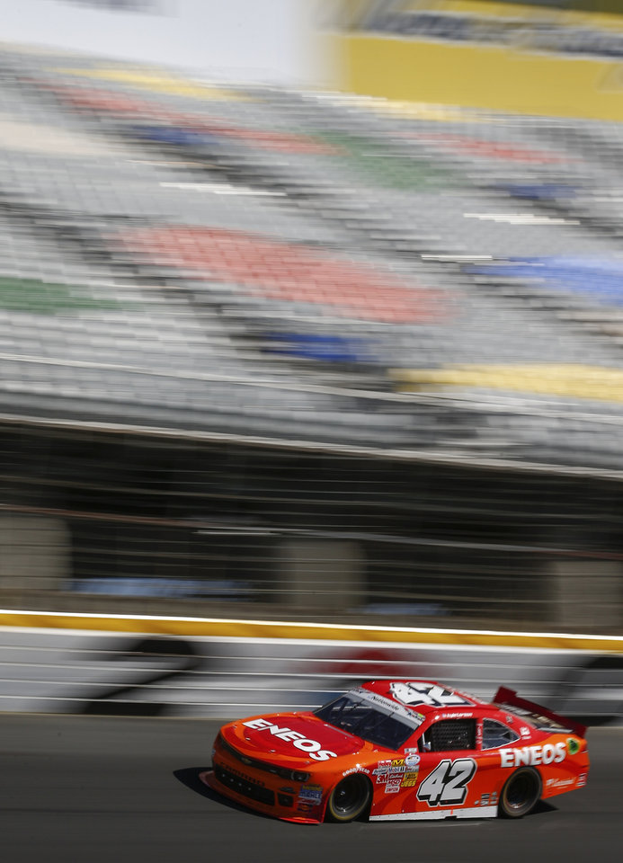 Photo - In this image taken with a slow shutter speed, Kyle Larson (42) races along at the top of Turn 2 during the NASCAR Nationwide series History 300 auto race at Charlotte Motor Speedway in Concord, N.C., Saturday, May 24, 2014. Larson won the race (AP Photo/Chris Keane)