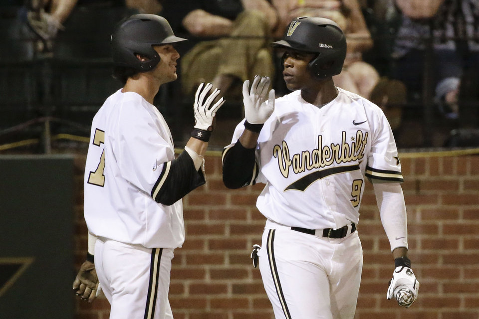 Photo - Vanderbilt's Dansby Swanson (7) is congratulated by Xavier Turner (9) after Swanson scored against Xavier in the seventh inning of an NCAA college baseball regional tournament game Friday, May 30, 2014, in Nashville, Tenn. (AP Photo/Mark Humphrey)