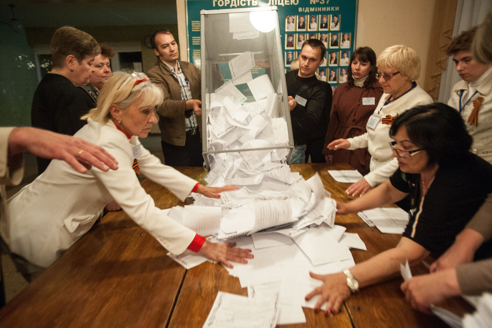 Photo - Members of election committee empty a ballot box after voting closed at a polling station in Donetsk, Ukraine, Sunday, May 11, 2014. Voters in two insurgent Ukrainian regions cast ballots Sunday on whether to declare their areas sovereign republics, a move denounced by the central government and likely to deepen the turmoil in the largely Russian-speaking east. (AP Photo/Evgeniy Maloletka)