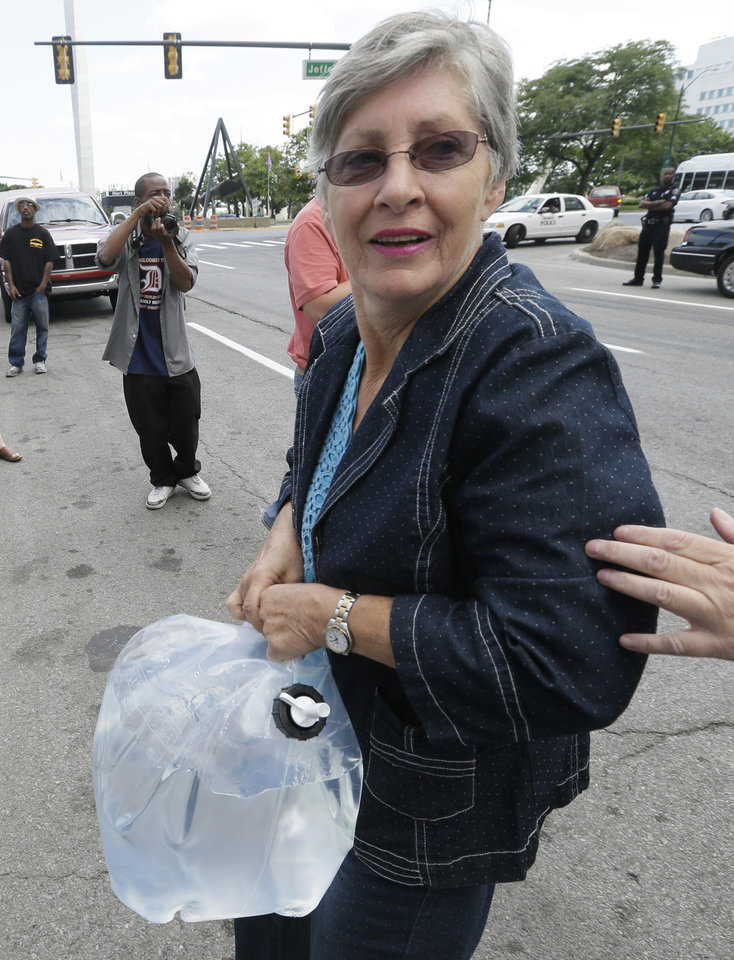 Photo - Claire McAllister, a Canadian who helped bring 1,000 liters (264 gallons) of water from Windsor, Ontario, to Detroit to protest thousands of residential service shutoffs by Detroit's water department, carries a container of water at a rally outside Detroit City Hall in Detroit, Thursday, July 24, 2014. (AP Photo)