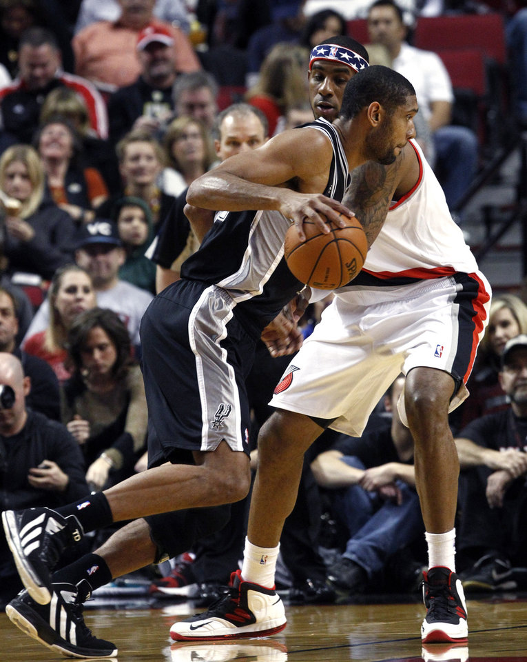 San Antonio Spurs forward Tim Duncan, left, drives on Portland Trail Blazers forward LaMarcus Aldridge during the first half of their NBA basketball game in Portland, Ore., Saturday, Nov. 10, 2012. (AP Photo/Don Ryan)