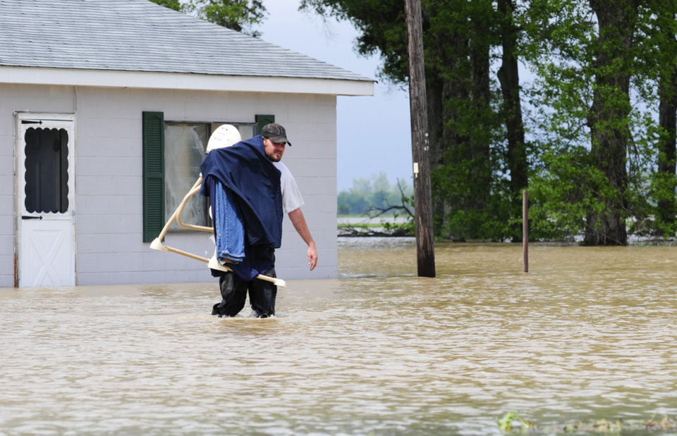 Photo - Randy German of Qulin, Mo., carries items from his flooded house along Highway 53 Wednesday, April 27, 2011. (AP Photo/Daily American Republic, Paul Davis)