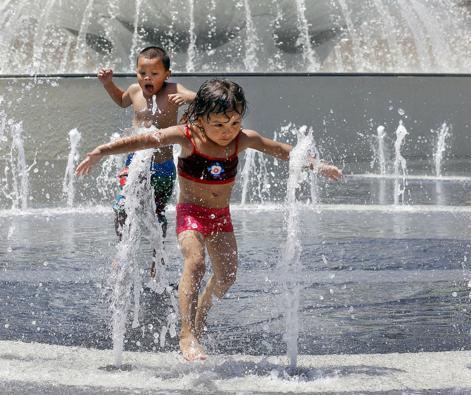 Photo - Mya Faggiani, 3, and her 5-year-old brother Javier, visiting from Las Vegas, enjoy cooling off in the fountains in Grand park in downtown Los Angeles Monday, May 13, 2013.  Unseasonably warm temperatures for May were common all over Southern California, nearing or exceeding the 100-degree Fahrenheit mark. (AP Photo/Nick Ut)