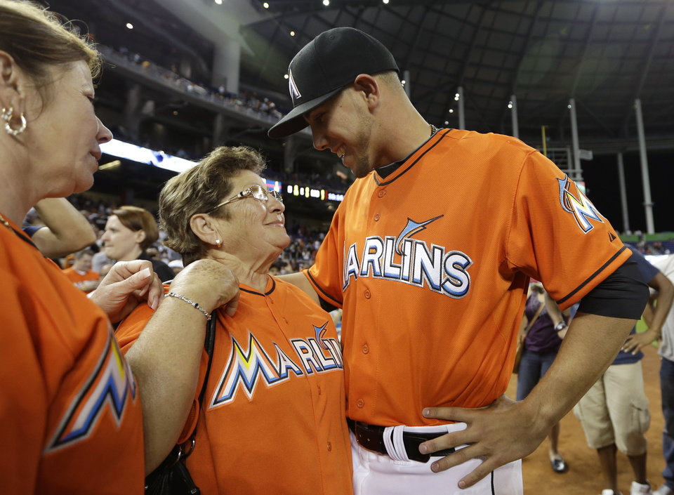 Photo - Miami Marlins starting pitcher Jose Fernandez, right, talks with his grandmother Olga Fernandez, of Cuba, center, and mother Maritza Fernandez, left, of Miami, following the Marlins' 10-1 victory over the Colorado Rockies in an opening day baseball game, Monday, March 31, 2014, in Miami. (AP Photo/Lynne Sladky)