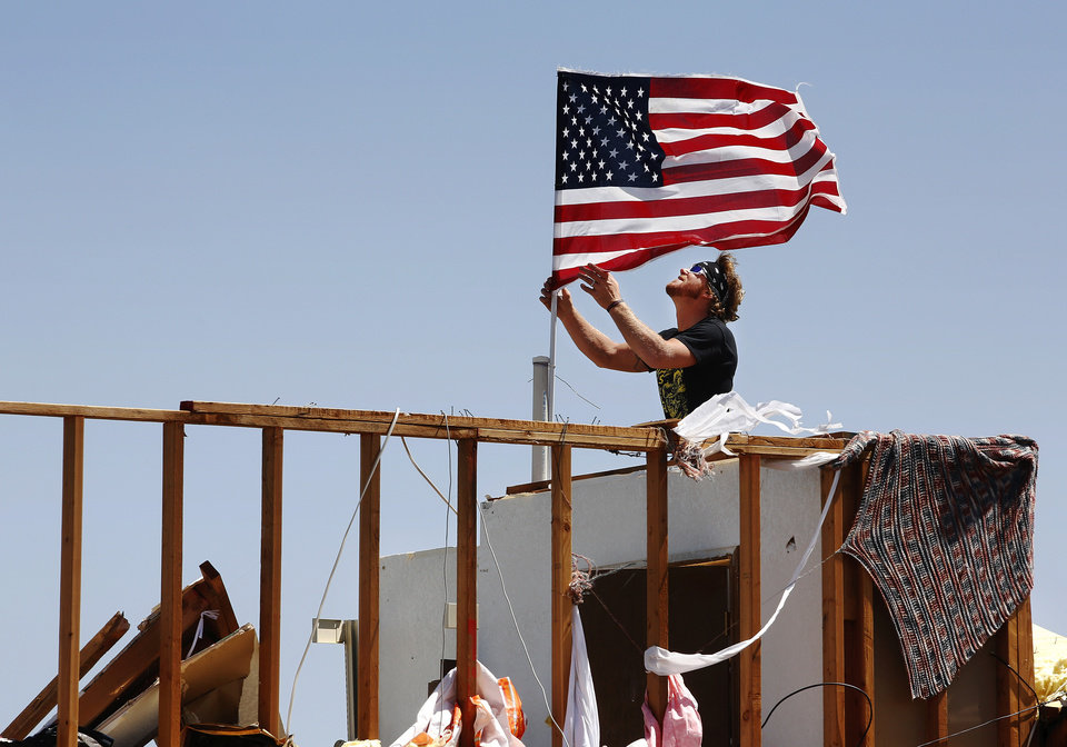 Photo - Derick (cq) Holman anchors an American flag in the wood of a remaining upstairs wall of Kay and Bonnie Meritt's home at 20545 SW 15 in Union City on Saturday, June 1, 2013. Derick is a friend of the couple's son, Kris Meritt, and was helping save items from the damaged home when he found the flag and, in an impromptu ceremony, placed it on the home's highest  point. Bonnie Meritt said nine homes near her, including hers, were damaged or destroyed in Friday night's tornado. They have lived in this house since 1996. The couple was unharmed. They took shelter inside the Union City fire station before the tornado hit. Photo  by Jim Beckel, The Oklahoman.