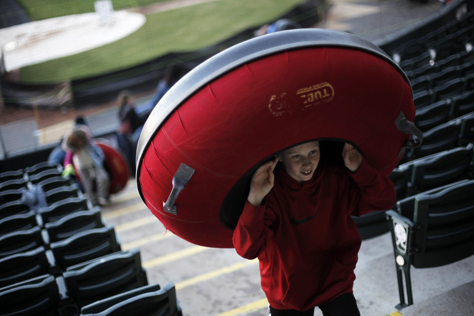 Caleb Edwards, 11, carries his tube up to take another ride of the snow slope at Chickasaw Bricktown Ballpark in Oklahoma City, Saturday, Nov. 24, 2012.  Photo by Garett Fisbeck, The Oklahoman