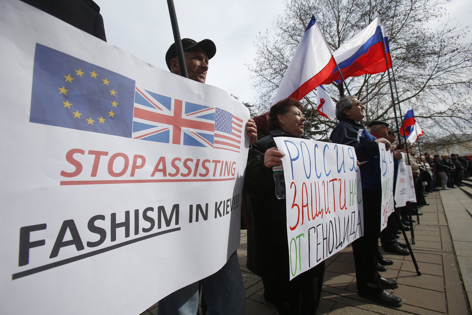 Photo - Pro-Russia demonstrators hold Russian and Crimean flags and posters as they rally in front of the local parliament building in Crimea's capital Simferopol, Ukraine, Thursday March 6, 2014. About 50 people rallied outside the local parliament Thursday morning waving Russian and Crimean flags. Lawmakers in Crimea called a March 16 referendum on whether to break away from Ukraine and join Russia instead, voting unanimously Thursday to declare their preference for doing so. A poster reads