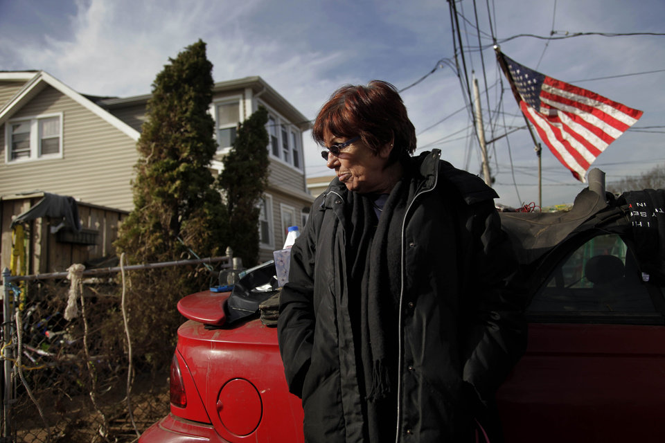 FILE - In this Nov. 20, 2012 file photo, Marge Gatti stands in front of her home, which was damaged by Superstorm Sandy, in the Midland Beach section of the Staten Island borough of New York. Six months after the storm, Gatti, the matriarch of her family, said �The whole family's separated, and it's terrible, you know?� The flood-soaked place was demolished months ago, and they're waiting for a government buyout. Now the family is scattered across New Jersey, New York and Texas.   (AP Photo/Seth Wenig, File)