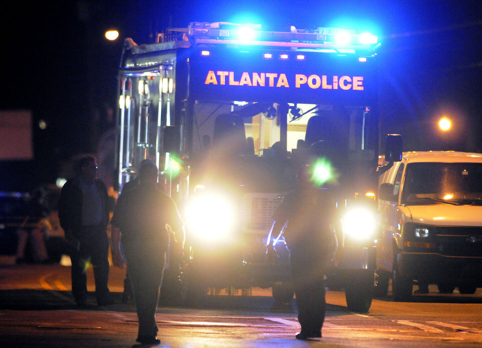 Photo -   Law enforcement personnel investigate the scene of an Atlanta Police Department helicopter crash early Sunday, Nov. 4, 2012, that killed two officers aboard the aircraft when it crashed near a shopping center late Saturday, Nov. 3, 2012. (AP Photo/David Tulis)