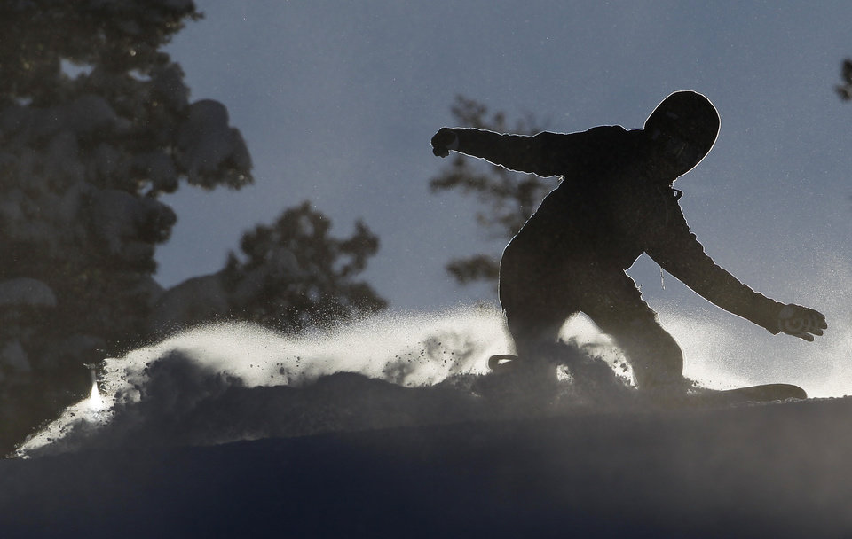 Photo - A snowboarder, silhouetted by the setting sun, kicks up a wake of snowy mist, at Winter Park alpine resort, in Colorado, Thursday Dec. 20, 2012. Fresh snow earlier in the week, with more expected before Christmas, has left much of Colorado ski-country replenished after a relatively warm and dry Fall. (AP Photo/Brennan Linsley)
