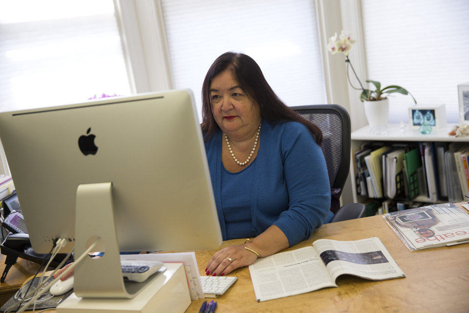 Photo - Jane Delgado, president of the National Alliance for Hispanic Health, works in her office in Washington, Monday, March 24, 2014. The nation's largest minority group risks being left behind by President Barack Obama's health care overhaul. Hispanics account for nearly one-third of the nation's uninsured, but all signs indicate that they remain largely on the sidelines as the White House races to meet a goal of 6 million sign-ups with less than a week to enroll. (AP Photo/ Evan Vucci)