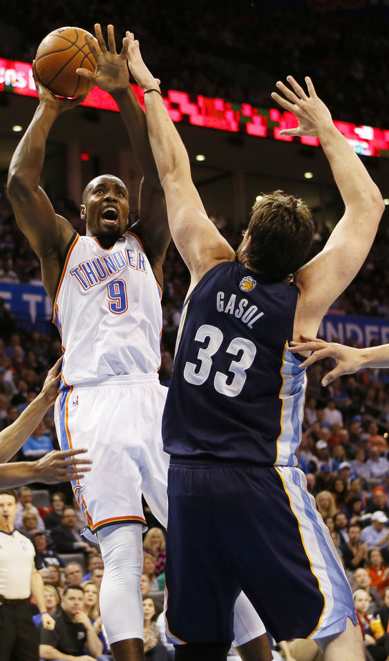 Photo - Oklahoma City's Serge Ibaka (9) shoots against Memphis' Marc Gasol (33) during an NBA basketball game between the Memphis Grizzlies and the Oklahoma City Thunder at Chesapeake Energy Arena in Oklahoma City, Friday, Feb. 28, 2014. Photo by Nate Billings, The Oklahoman