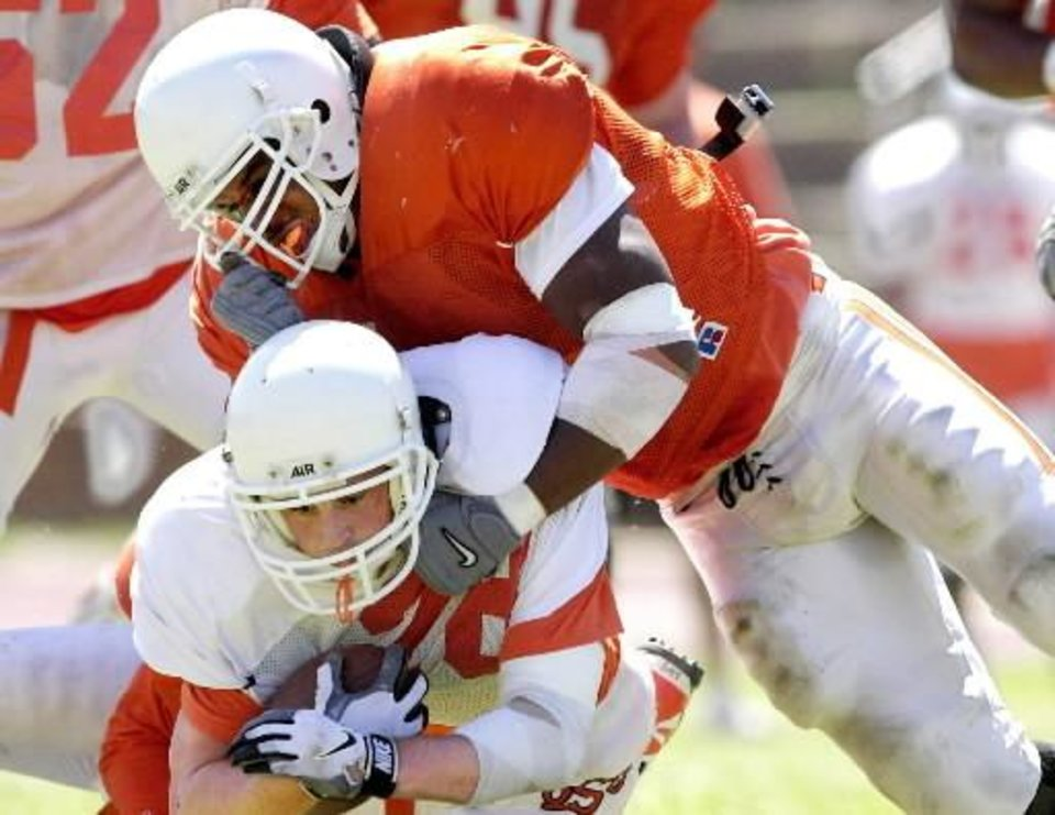 Photo - Michael Cox tackles  Richard  Schwarz during OSU's spring football scrimmage at Taft stadium. 2000 file photo by Bryan Terry