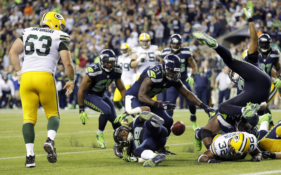 Photo -   Seattle Seahawks players eye a fumble by Green Bay Packers' Cedric Benson (32), lower right, that was recovered by Packers' Jeff Saturday (63) in the second half of an NFL football game, Monday, Sept. 24, 2012, in Seattle. The Seahawks defeated the Packers 14-12. (AP Photo/Ted S. Warren)
