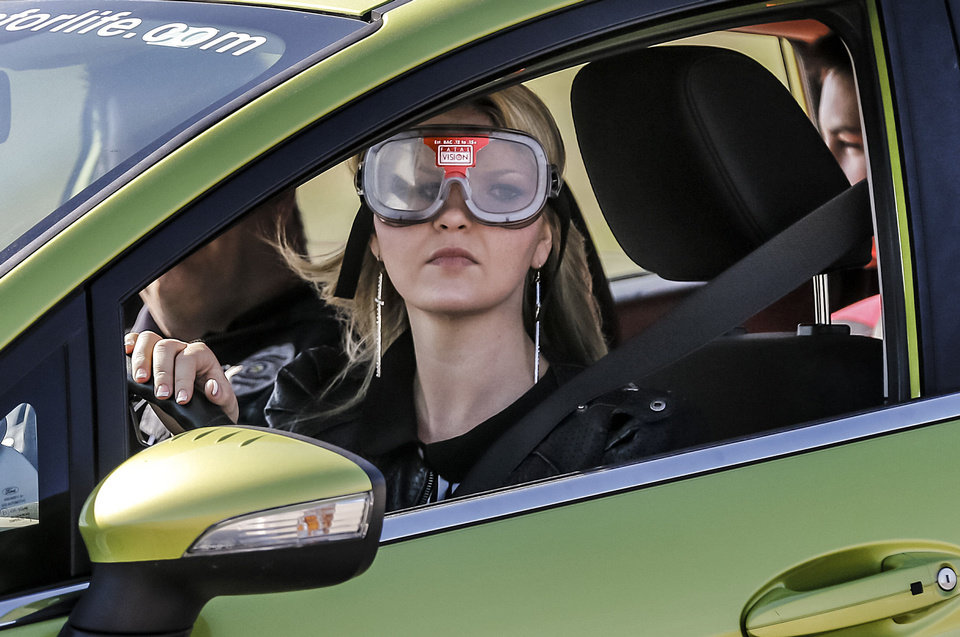 "Anna Milnes wears ""drunk goggles"" as she tries to drive through a parking lot  during Ford Driving Skills for Life at Yukon High School on Thursday. Photo by Chris Landsberger, The Oklahoman <strong>CHRIS LANDSBERGER - CHRIS LANDSBERGER</strong>"