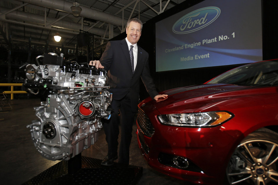 Photo - Joe Hinrichs, Ford's President of the Americas, poses with the 2.0-liter EcoBoost engine at the Ford Cleveland Engine Plant, Thursday, Feb. 21, 2013, in Brook Park, Ohio. Ford is moving production of a popular small engine from Spain to Cleveland as sales of four-cylinder motors continue to rise. (AP Photo/Tony Dejak)