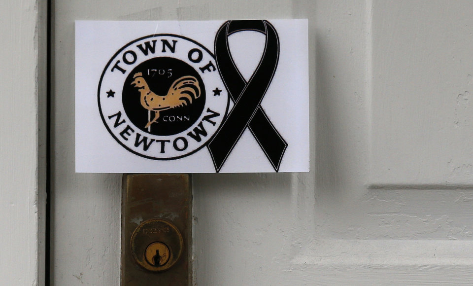Photo - A sign showing the town seal and a black ribbon is posted on the door of an antique colonial home in the historic district near the funeral for six-year-old student shooting victim Jack Pinto in Newtown, Conn., Monday, Dec. 17, 2012. A gunman opened fire at Sandy Hook Elementary School in the town, killing 26 people, including 20 children before killing himself on Friday. (AP Photo/Charles Krupa) ORG XMIT: CTCK109