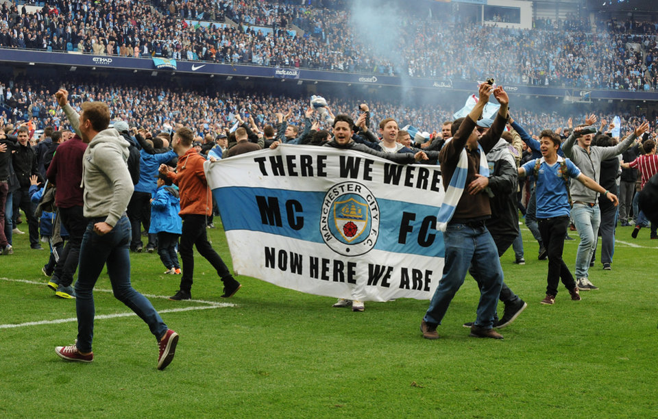 Photo - Manchester City's fans invade the pitch after the final whistle, as Manchester City are crowned Premier League Champions after the English Premier league soccer match between Manchester City and West Ham United at the Etihad Stadium,  Manchester, England, Sunday, May 11, 2014. (AP Photo/Rui Vieira)