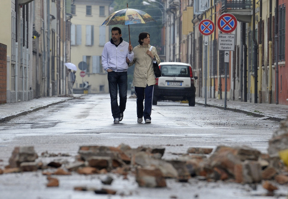 Photo -   Residents view damage caused by a magnitude-6.0 temblor in Finale Emilia northern Italy, Sunday, May 20, 2012. One of the worst quakes to hit northeast Italy in hundreds of years rattled the region around Bologna early Sunday, killing at least four people, collapsing factories and sending residents running out into the streets, emergency services said. (AP Photo/Marco Vasini)
