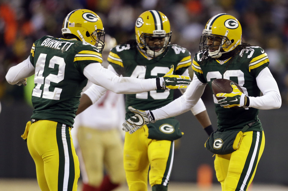 Photo - Green Bay Packers cornerback Tramon Williams (38) celebrates an interception with strong safety Morgan Burnett (42) and free safety M.D. Jennings (43) during the first half of an NFL wild-card playoff football game against the San Francisco 49ers , Sunday, Jan. 5, 2014, in Green Bay, Wis. (AP Photo/Jeffrey Phelps)