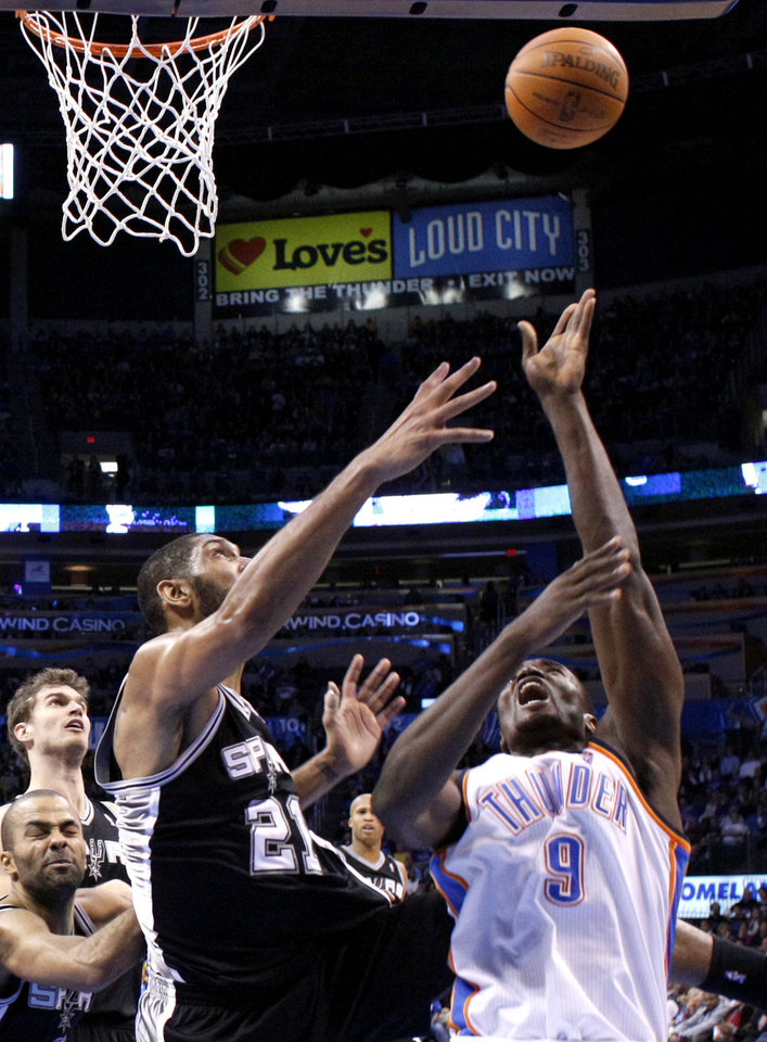 Oklahoma City Thunder's Serge Ibaka (9) shoots over San Antonio Spurs' Tim Duncan (21) during the the NBA basketball game between the Oklahoma City Thunder and the San Antonio Spurs at the Chesapeake Energy Arena in Oklahoma City, Sunday, Jan. 8, 2012. Photo by Sarah Phipps, The Oklahoman