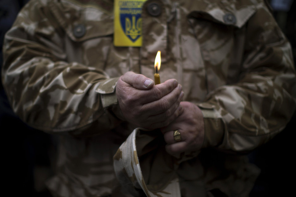 Photo - A man wearing camouflage uniform holds a candle during the funeral of Volodymyr Topiy, 59, who was found burned in the house of trade unions in Kiev's Independence Square during recent clashes with police, Ukraine, Tuesday, March 4, 2014. Vladimir Putin ordered tens of thousands of Russian troops participating in military exercises near Ukraine's border to return to their bases as U.S. Secretary of State John Kerry was on his way to Kiev. Tensions remained high in the strategic Ukrainian peninsula of Crimea with troops loyal to Moscow fired warning shots to ward off protesting Ukrainian soldiers. (AP Photo/Emilio Morenatti)