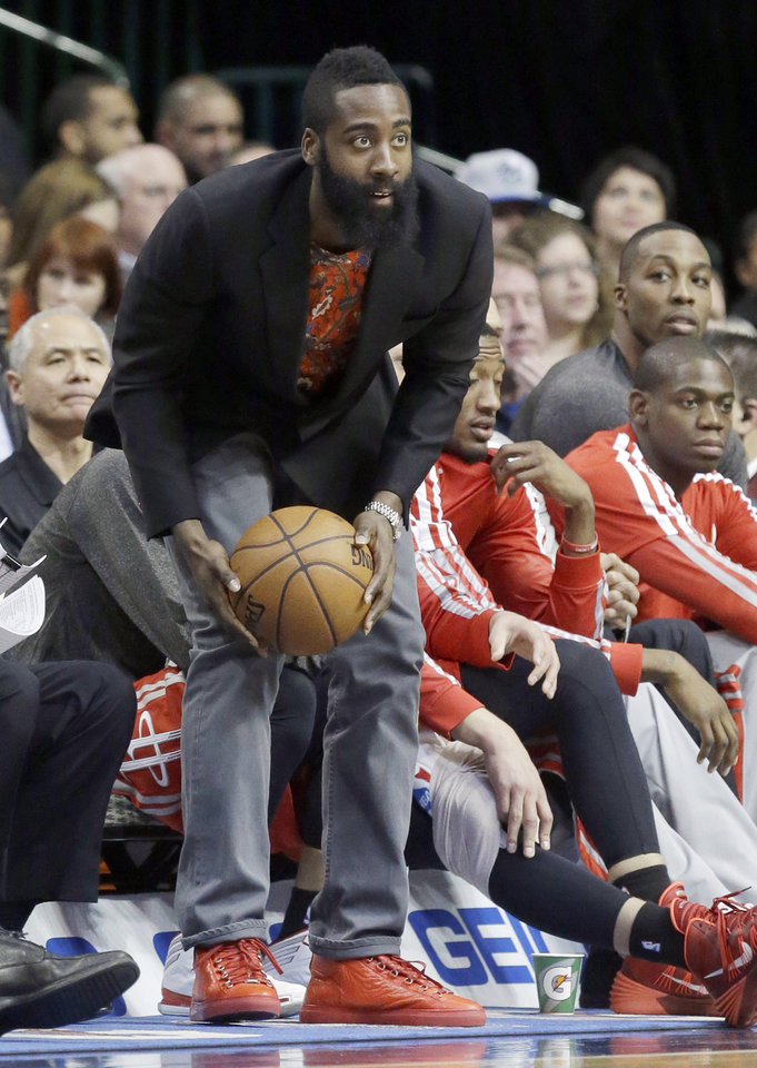 Photo - Houston Rockets shooting guard James Harden catches the game ball from the bench during the first half of an NBA basketball game against the Dallas Mavericks, Wednesday, Jan. 29, 2014, in Dallas. Harden did not suit up to play. (AP Photo/LM Otero)