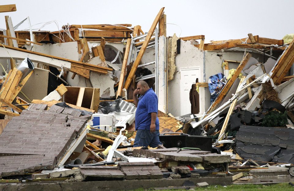 Photo -   Juan Ventura stands inside what remains of his home as he talks with his father on his mobile phone Tuesday, April 3, 2012, in Forney, Texas. Ventura said that no one was home when the storm hit. (AP Photo/Tony Gutierrez)