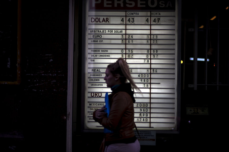 A woman passes a list of foreign currency exchange rates at an exchange house in Buenos Aires, Argentina, Wednesday, May 16, 2012. The AFIP tax collection agency's recent measure to control and approve every currency exchange operation in the country has made it practically impossible for Argentines to buy dollars, forcing them to get the currency on the black market. (AP Photo/Natacha Pisarenko)