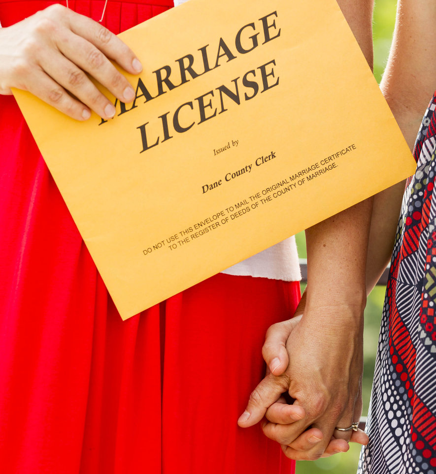 Photo - Kristen Walker, left, holds up wedding documents as she holds Jennifer Price's hand during their wedding ceremony Saturday, June 7, 2014, in Madison, Wis. On Friday a federal judge struck down the state's gay marriage ban. (AP Photo/Andy Manis)