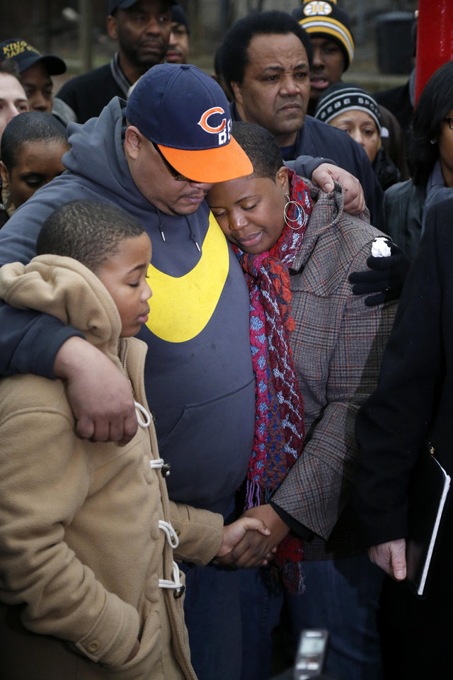 Nathaniel Pendelton, center, hugs his son Nathaniel Jr. and his wife Cleopatra during a news conference with Chicago Police Superintendent Garry McCarthy seeking help from the public in solving the murder of Pendelton's daughter Hadiya Wednesday, Jan. 30, 2013, in Chicago.  Hadiya, 15, who had performed in President Barack Obama's inauguration festivities, was killed in a Chicago park as she talked with friends by a gunman who apparently was not even aiming at her. The city's 42nd slaying is part of Chicago's bloodiest January in more than a decade, following on the heels of 2012, which ended with more than 500 homicides for the first time since 2008. It also comes at a time when Obama, spurred by the Connecticut elementary school massacre in December, is actively pushing for tougher gun laws. (AP Photo/Charles Rex Arbogast)