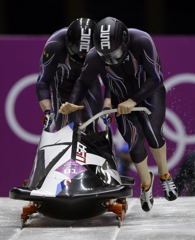 Photo - The team from the United States USA-1, piloted by Steven Holcomb and brakeman Steven Langton, start their first run during the men's two-man bobsled competition at the 2014 Winter Olympics, Sunday, Feb. 16, 2014, in Krasnaya Polyana, Russia. (AP Photo/Dita Alangkara)