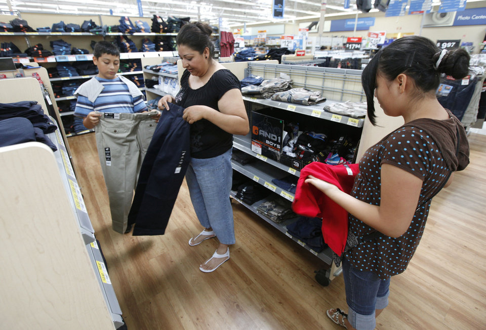 Photo - Patricia Gaucin shops for school uniforms for her children Eddie, 13, and Iris, 16, at the Walmart store at 100 E. I-240 Service Road in south Oklahoma City. This upcoming weekend will be sales tax free for purchases involving back-to-school supplies. Photo by Paul Hellstern, The Oklahoman  PAUL HELLSTERN - Oklahoman