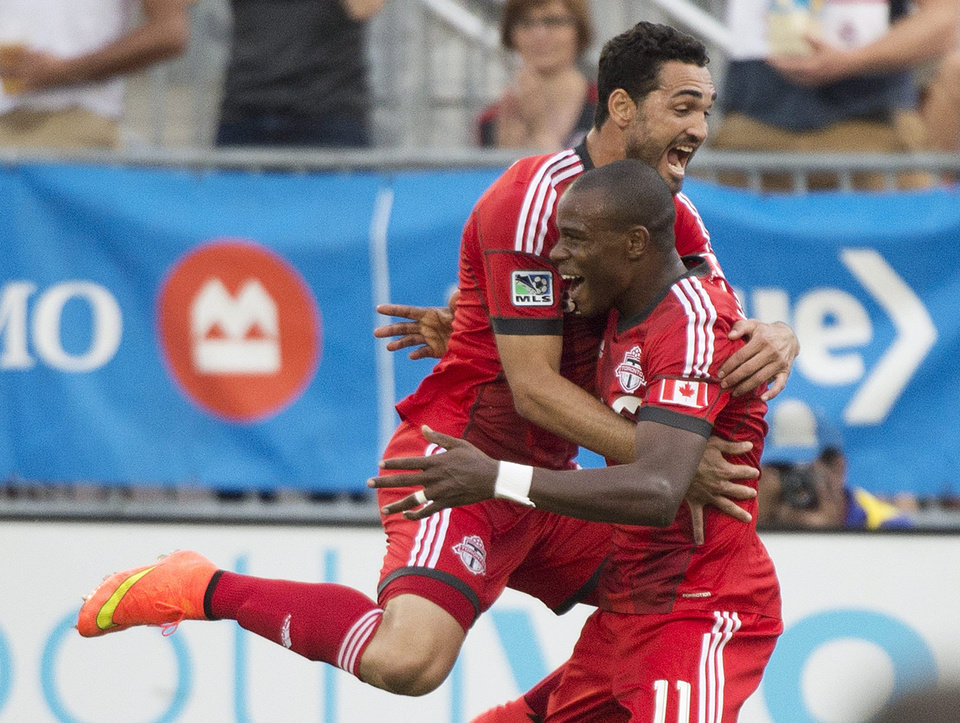 Photo - Toronto FC midfielder Jackson, right, celebrates with teammate Gilberto, left, after scoring against Sporting Kansas City during the first half of an MLS soccer game Saturday, July 26, 2014, in Toronto. (AP Photo/The Canadian Press, Nathan Denette)